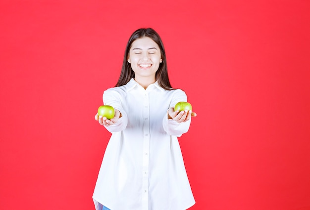 Girl in white shirt holding green apples in the hand and offering them to the customer