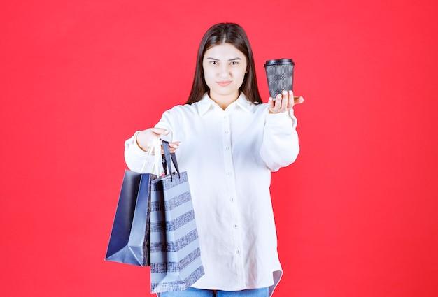 Ragazza in camicia bianca che tiene più borse della spesa e condivide con una tazza di caffè da asporto nera