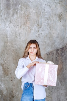 Girl in white shirt holding a pink gift box wrapped with white ribbon and looks confused and hesitating.