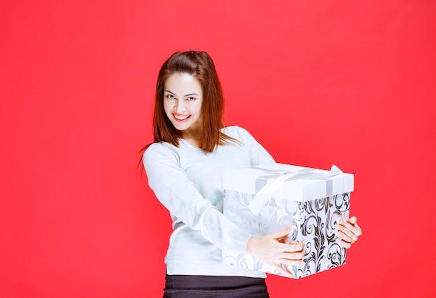 Ragazza in camicia bianca con in mano una scatola regalo stampata