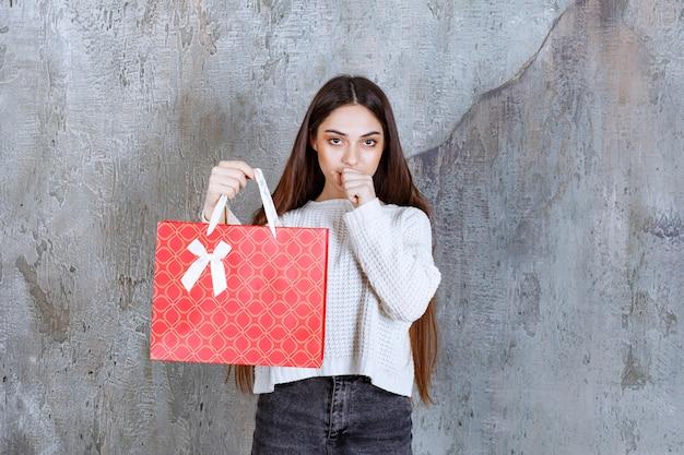 Ragazza in camicia bianca che tiene una borsa della spesa rossa e sembra confusa e premurosa.