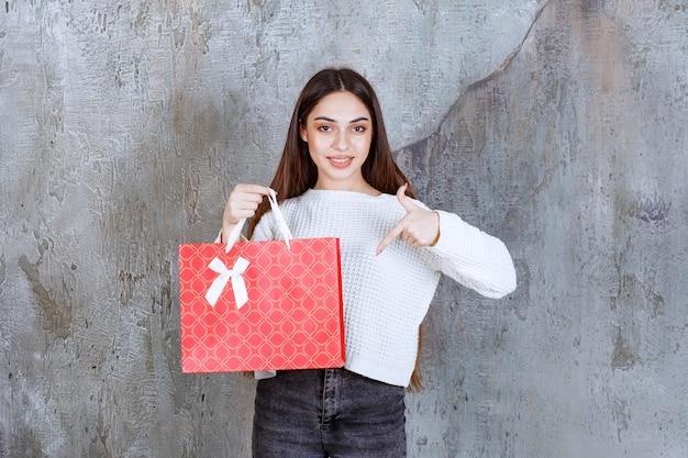 Ragazza in camicia bianca che tiene una borsa della spesa rossa.