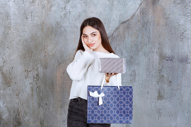 Girl in white shirt holding a silver gift box and a blue shopping bag and looking confused and thoughtful about making a choice.