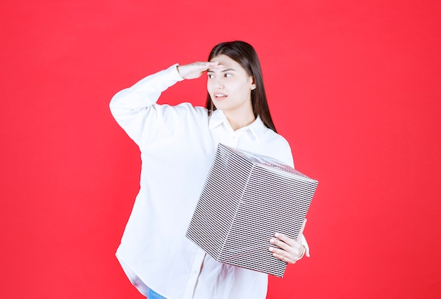 Ragazza in camicia bianca con in mano una scatola regalo d'argento, guardando e chiamando qualcuno