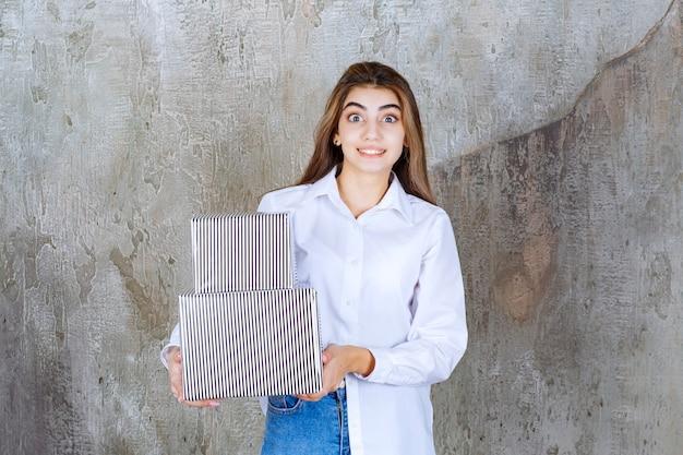 Ragazza in camicia bianca che tiene scatole regalo d'argento e sembra confusa e sorpresa.