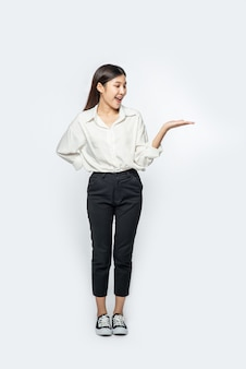The girl in a white shirt holding something