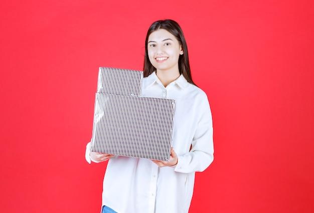 Ragazza in camicia bianca con in mano due scatole regalo d'argento