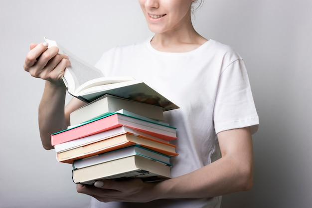 Girl in a white shirt holds a lot of books in the hands. reading, page turning