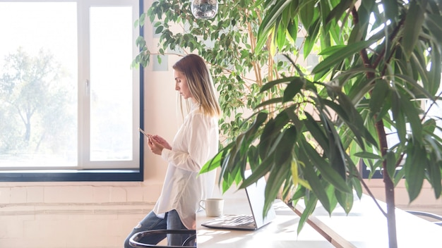 A girl in a white shirt is looking at smartphone between freelancer work.