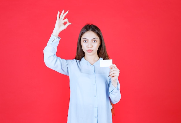 Ragazza in camicia bianca che presenta il suo biglietto da visita e che mostra il segno positivo della mano.
