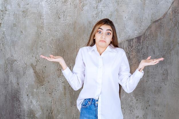 Ragazza in camicia bianca in piedi su un muro di cemento e sembra confusa e premurosa.