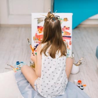 Ragazza in bianco seduto sul pavimento e dipinto con tempera