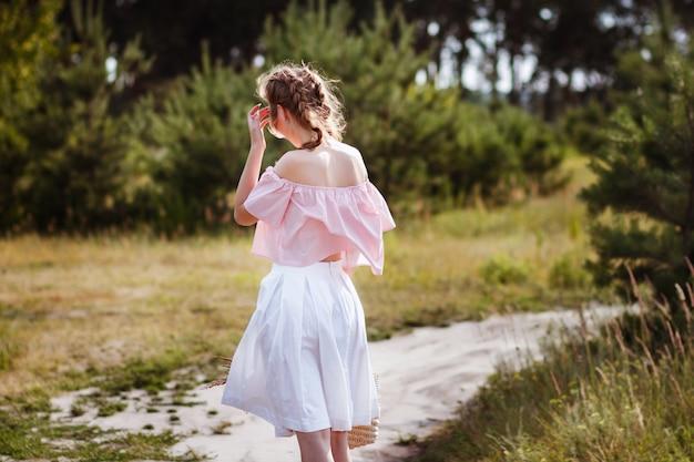Girl in a white skirt walks in the summer. her hair develops the wind