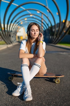 Girl in white stockings sit on longboard and listening music
