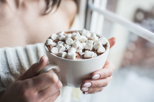 Girl in a white sweater holds a cup of hot chocolate with marshmallows and warms her hands staying near a window. face is not visible.