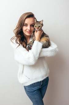 Girl in a white sweater hugs a gray cat on a white