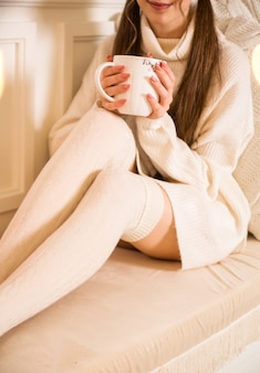 A girl in a white sweater and leggings holds a large white cup in her hands