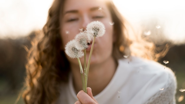 Girl in white t-shirt blowing dandelions