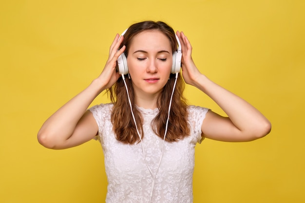 A girl in a white t-shirt and brown jeans on a yellow background relaxes and carefully listens and enjoys the music in the white headphones closing her eyes.