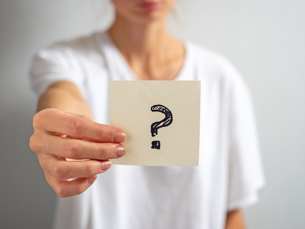 A girl in a white t-shirt holds a paper sticker with a question mark in her hand. focus on the sticker, blurred background.