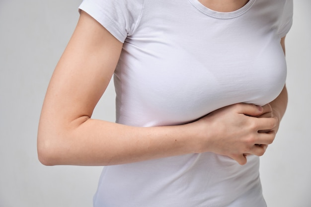 A girl in a white t-shirt is massaging under her breasts. the concept of intercostal neuralgia.