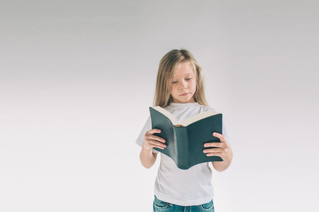 Girl in white t-shirt is reading a book