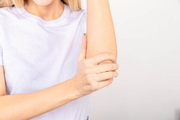 A girl in a white t-shirt massages her elbow from acute pain in the joint.