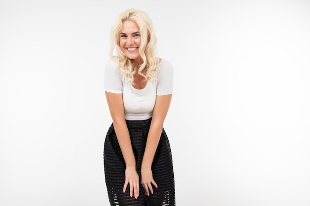 Girl in a white tank top and black skirt laughs on a white with copy space