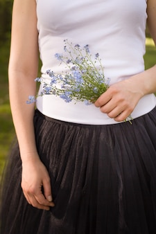 Girl in a white tshirt and black fluffy skirt holding a beautiful bouquet of forget me not flowers