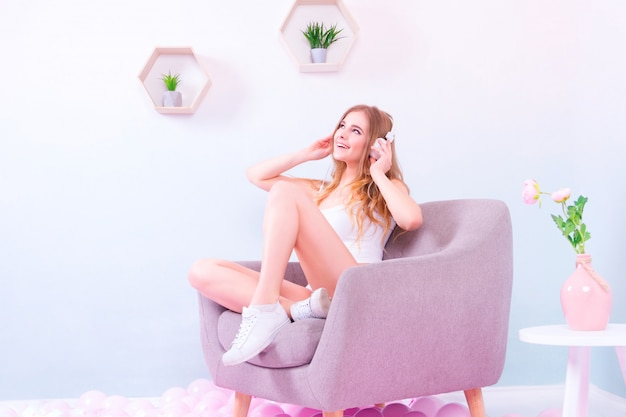 Girl in white underwear and white sneakers sitting in lotus pose on the purple armchair
