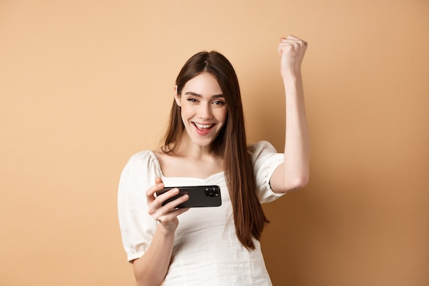 携帯電話で勝つ女の子。幸せな女性が手を上げて、喜びでイエスを叫び、ベージュの上に立って、スマートフォンアプリで目標を達成します。