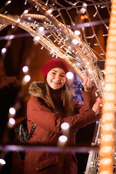 Girl in winter clothes over lights background, near christmas tree lights