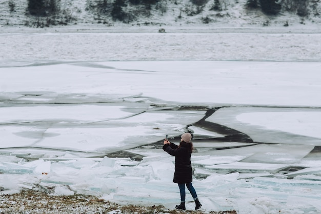 A girl in winter clothes takes a selfie against the background of cracked ice on the river.