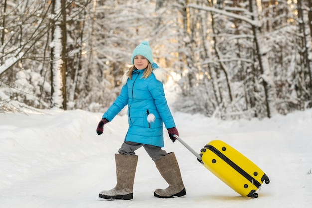 A girl in winter in felt boots goes with a suitcase on a frosty snowy day.