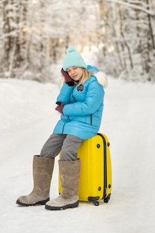 A girl in winter in felt boots sits on a suitcase on a frosty snowy day.