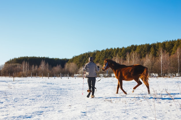 The girl in the winter field is engaged in training with her foal