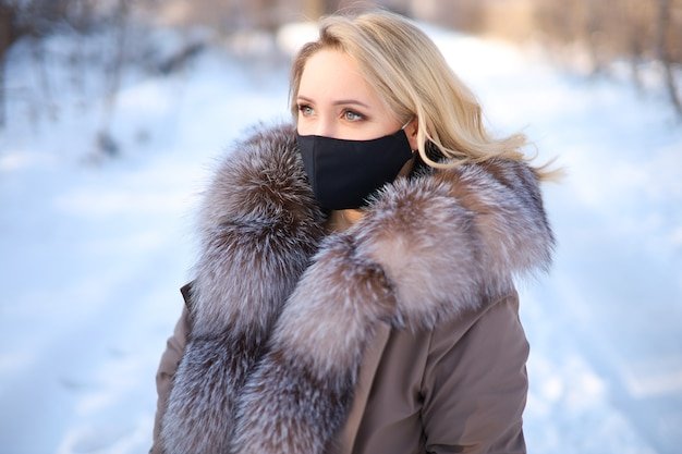 A girl in a winter fur coat with a black protective mask on her face
