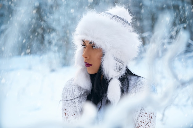 Girl in winter hat on winter blurred background.
