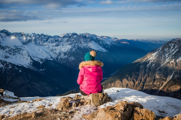 Girl in a winter jacket and hat looking at the snowy mountains