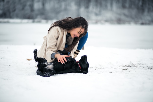 Girl in winter playing with dog