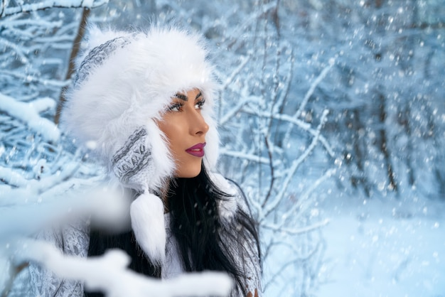 Girl in winter white hat in forest with snow near trees.