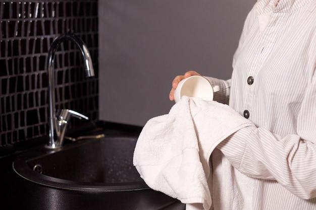 Девушка вытирает посуду и чашки с подставкой для полотенец у раковины на кухне дома