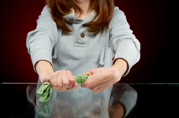 Girl wipes the glass on the counter with a damp green cloth on a red