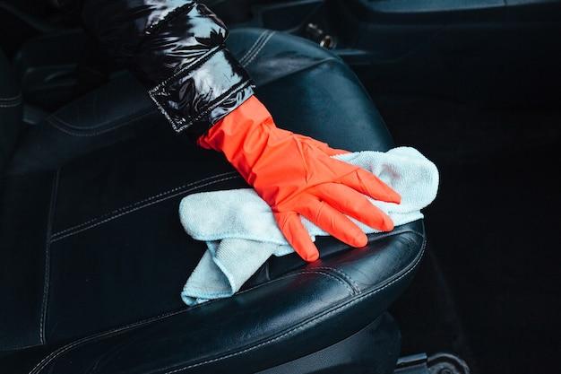 車のインテリアのクローズアップを拭く女の子
