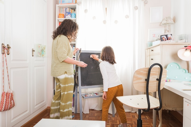 Girl wiping chalkboard for mother