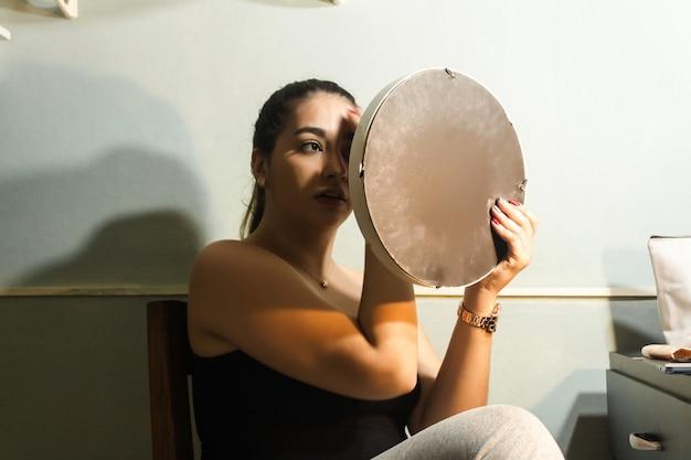Девушка вытирает лицо, чтобы начать мириться в своей комнате.