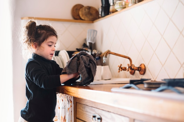 Girl wiping her hand with towel in kitchen