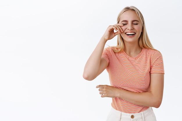 열심히 웃다가 눈물을 닦으며 유쾌한 코미디를 즐기는 소녀. 줄무늬 티셔츠를 입은 평온한 행복한 금발 여성은 재미 있고, 킥킥거리고, 스탠드업에 참석하고, 밝은 흰색 배경에 서 있습니다.