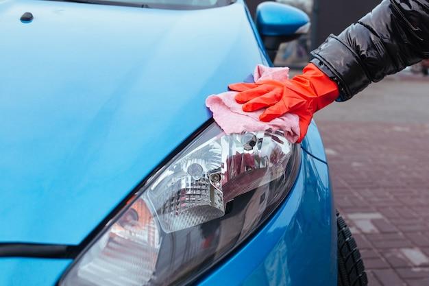 車のクローズアップのヘッドライトを拭く少女