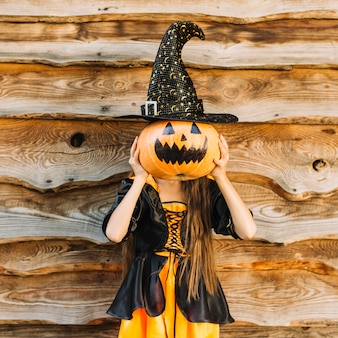 Girl in witch costume closing face by pumpkin with hat